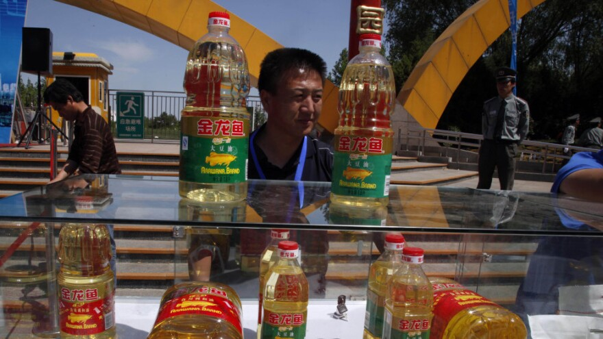 A Chinese man stands behind counterfeit cooking oil products placed next to the authentic ones during an event in Beijing Sunday to promote awareness of economic crimes.