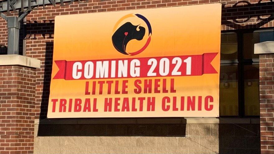 """A yellow sign contains the logo of a bison outline in black with a pink heart symbol on its chest sits within a circle of yellow, blue, red and black over the following words on a red banner, """"COMING 2021 Little Shell Tribal Health Clinic."""""""