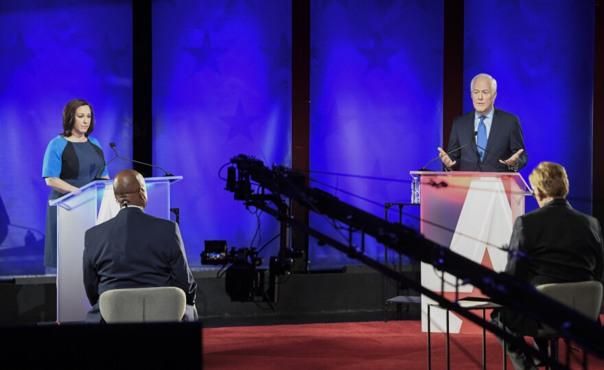Republican U.S. Sen. John Cornyn, of Texas, back right, speaks during a debate with MJ Hegar, of Round Rock, left. Both participants are wearing blue. And there's a large camera dolly in the shot. This debate was captured by KXAN in Ausitn.