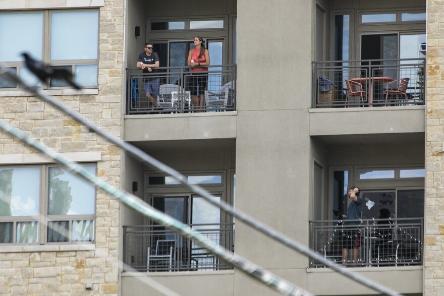 Austin residents watch a Thunderbirds flyover Wednesday afternoon from their apartment balconies.