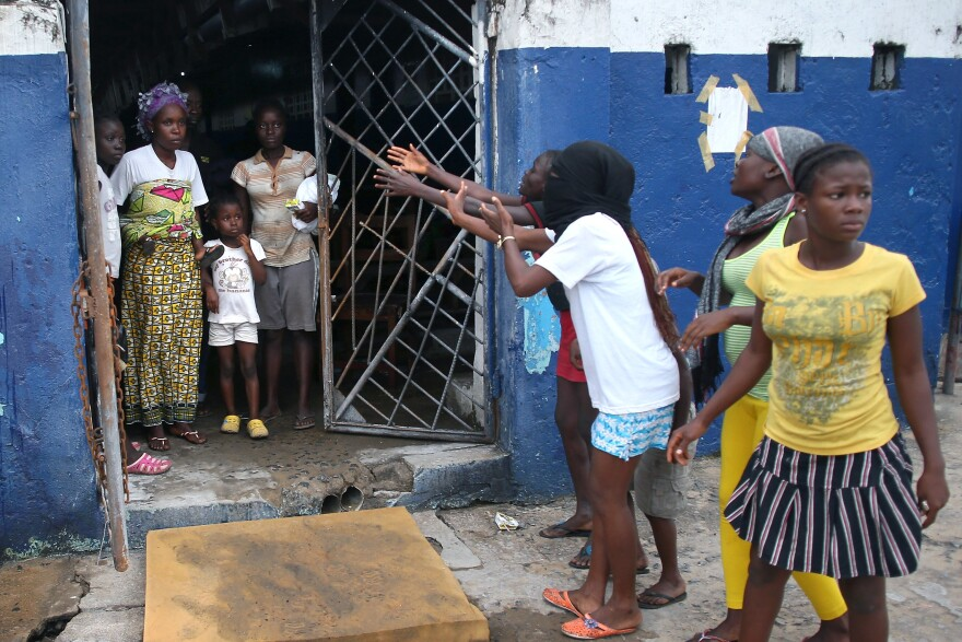 Residents beckon patients to leave the Ebola holding center.