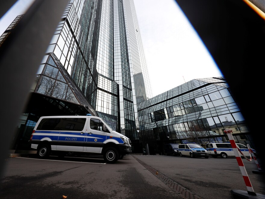 Police vehicles are parked in front of Deutsche Bank headquarters as roughly 170 officers, prosecutors and tax inspectors searched the bank's offices in and around Frankfurt, Germany, on Thursday.