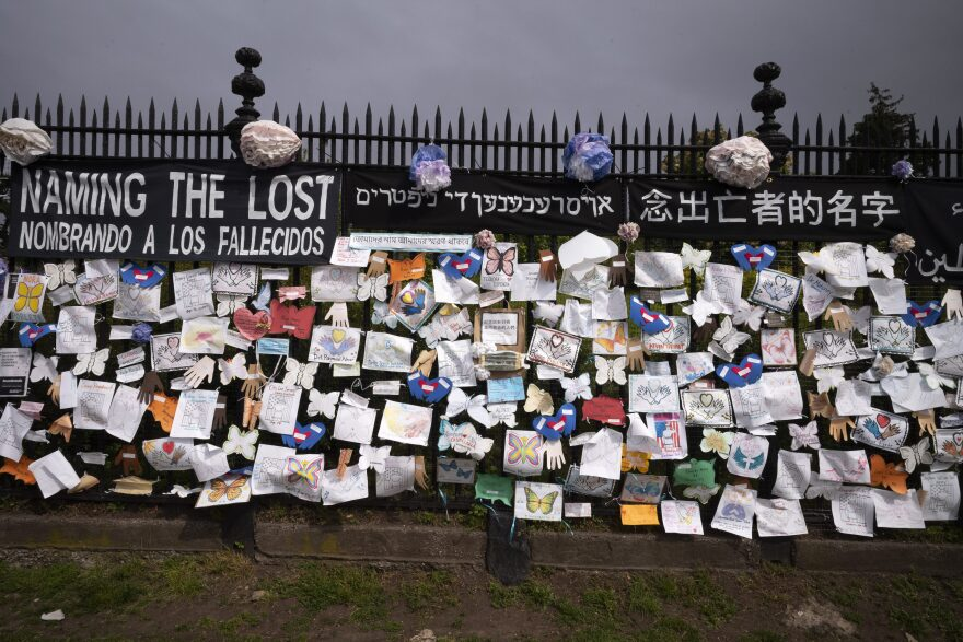A fence outside Brooklyn's Green-Wood Cemetery is adorned with tributes to victims of COVID-19 in New York. The memorial is part of the Naming the Lost project which attempts to humanize the victims who are often just listed as statistics. (Mark Lennihan/AP)