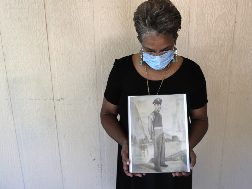 Belvin Jefferson White poses with a portrait of her father, Saymon Jefferson, who died from COVID-19, in Baton Rouge, La., in May.