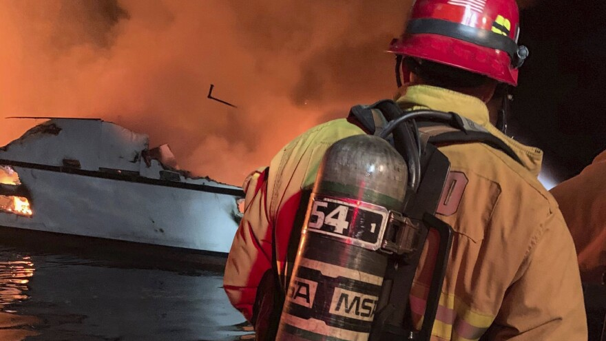 "Firefighters respond to a boat fire off the coast of Southern California on Monday. The U.S. Coast Guard said it launched several boats to help more than two dozen people ""in distress."""