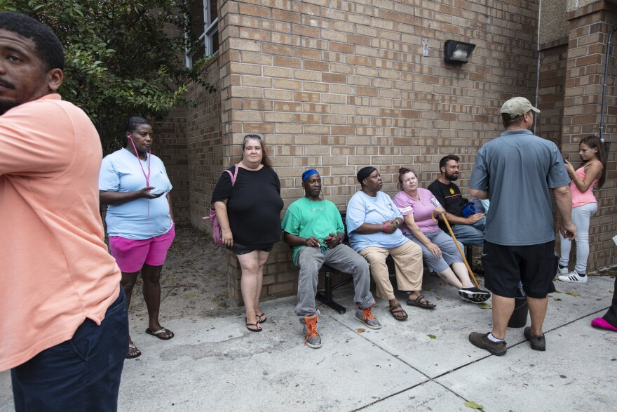 Hurricane evacuees relax Wednesday outside the temporary shelter at Trask Middle School in Wilmington, N.C., ahead of Florence's arrival.