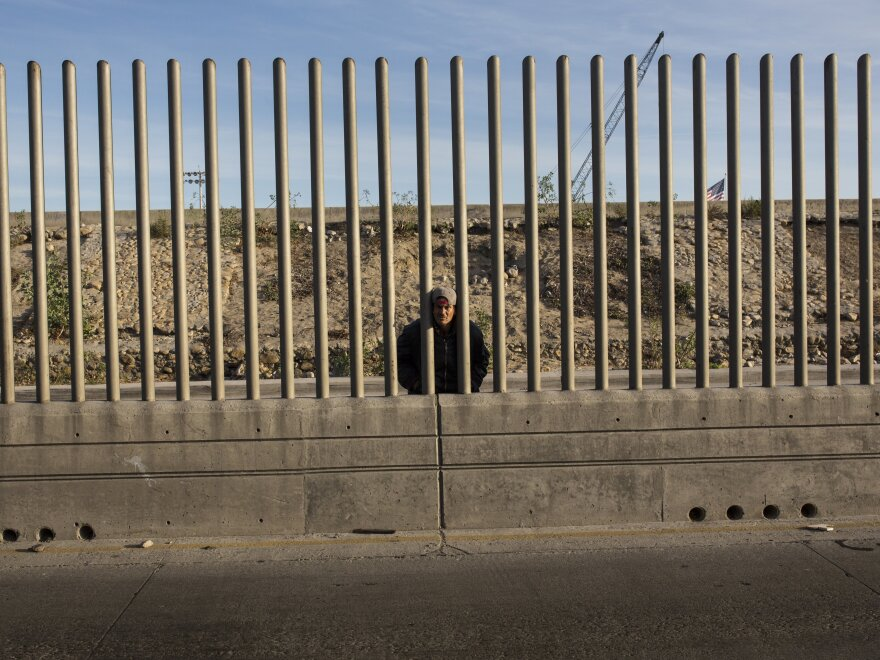 Issac Rodriguez, from Sinaloa, Mexico, peers through the fence that divides Mexico and the U.S. in Tijuana, Mexico.