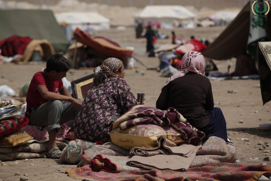 Syrian refugees sit among their belongings in the Kawrgosk refugee camp in Irbil, Northern Iraq.