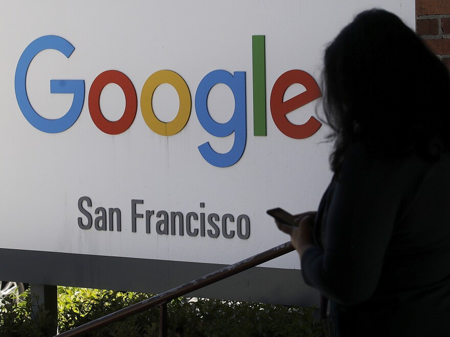 A woman walks past a Google sign in San Francisco. The Justice Department is launching an antitrust review of major online companies. The DOJ did not name the firms, but there have been increasing calls to regulate companies like Google, Facebook and Amazon.