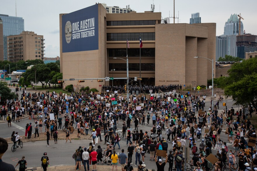 People protest in front of the Austin Police Department.
