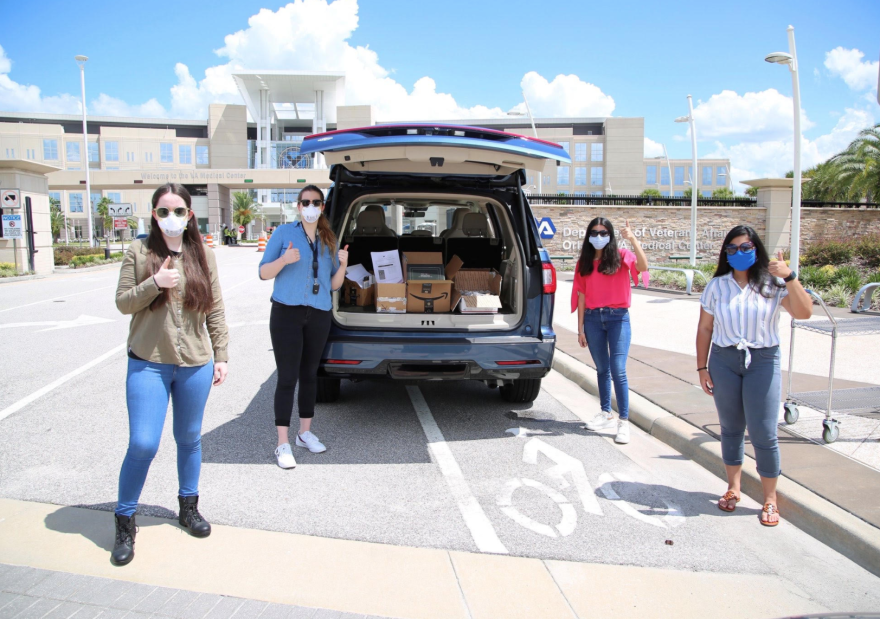A group of young women wearing masks give thumbs up while standing around a vehicle full of boxes.