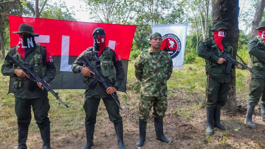 Colombian Soldier Fredy Moreno (center) who was captured by rebels of the National Liberation Army, is seen next to ELN members, before his release in Arauca, Colombia, on Feb. 6 2017.