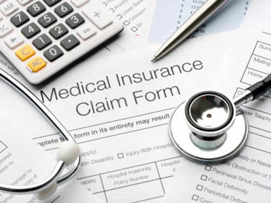 Medical Insurance Claim Form sorrounded by pen, calculator and stethoscope.