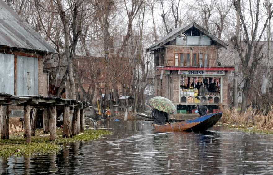 A vendor heads home from Dal Lake's floating wholesale produce market during an early February snowstorm.