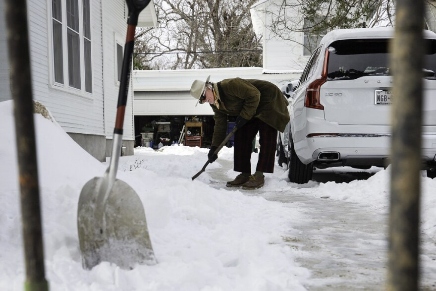 Byron Thomas shovels ice and snow from his driveway in the Hyde Park neighborhood of Austin Tuesday.