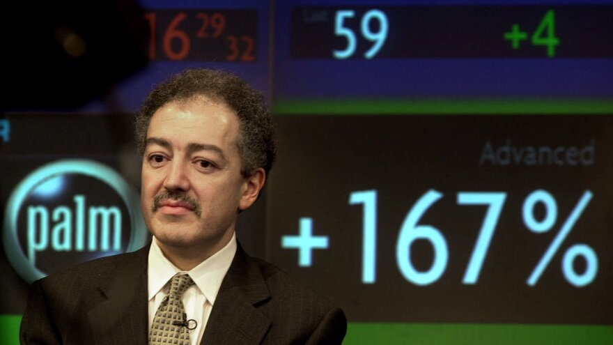 3Com's chief executive, Eric Benhamou, listens during an interview at Nasdaq television studios in New York on March 2, 2000. A stock ticker shows shares of Palm Inc., a spinoff of 3Com, soaring in opening trading on the Nasdaq Stock Market.