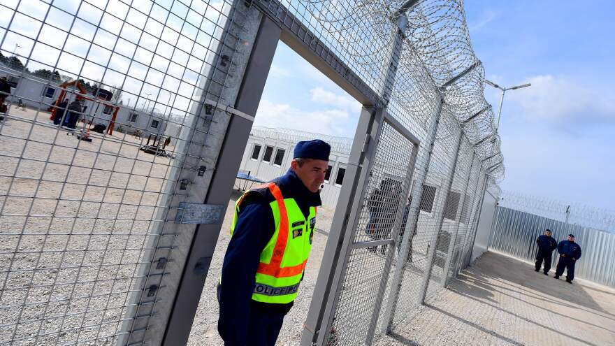 """A police officer walks through a gate at the Tompa border station transit zone in April 2017. Hungary has two """"transit zones"""" with shipping containers that are used to automatically detain migrants while their asylum claims are investigated. This month, Hungary began denying food to asylum-seekers whose claims were rejected and appealed, human rights groups say."""