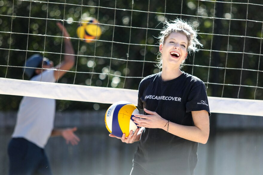 a woman holding a volleyball
