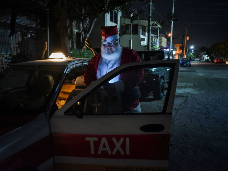Francisco Monzon, 50, a taxi driver dressed as Santa Claus, looks at his phone, in Boca del Rio, Veracruz state, Mexico, on Dec. 24, 2020.