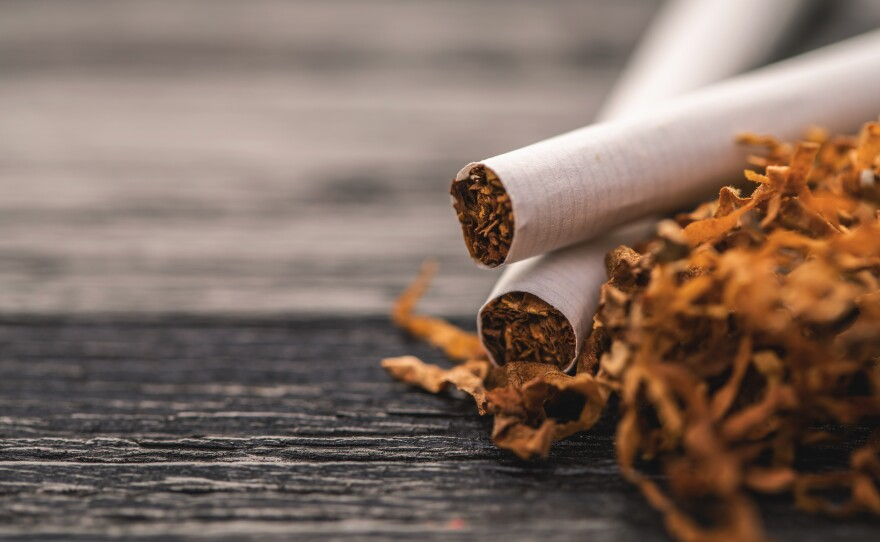 cigarettes and tobacco on a black wooden background