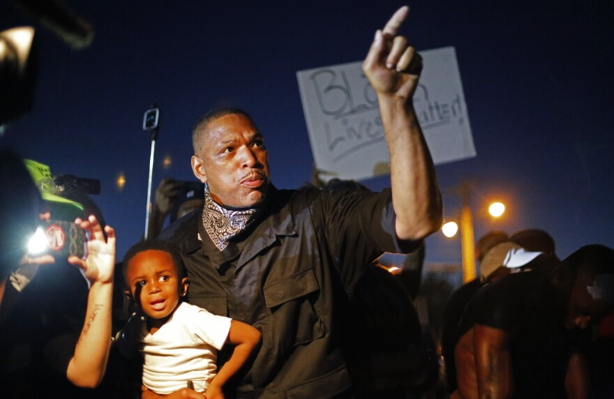 A father holds his son as he takes part in a demonstration in Ferguson, Mo., on Monday night. Police arrested more than 20 people in the city's streets Monday night; no violence or damage was reported.