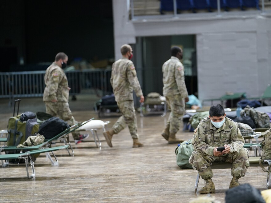 Members of the Louisiana National Guard prepare beds in a shelter ahead of Hurricane Delta, Friday in Lake Charles, La.