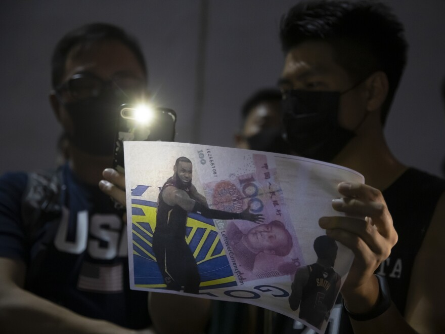 A demonstrator holds a sign showing Lebron James embracing a Chinese 100-yuan banknote during a rally in Hong Kong on Tuesday.