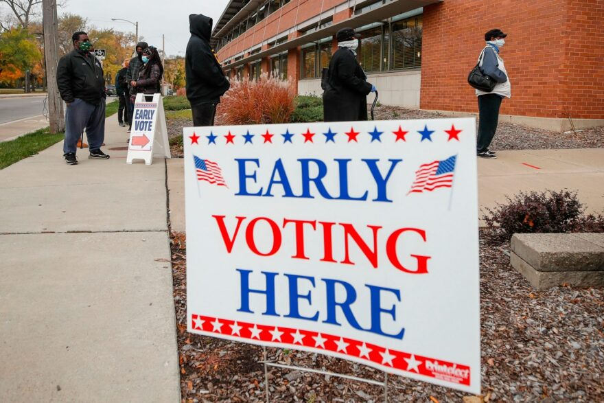 People wait in line outside the Washington Park Library to cast their ballots on the first day of in-person early voting for the elections in Milwaukee, Wisconsin.