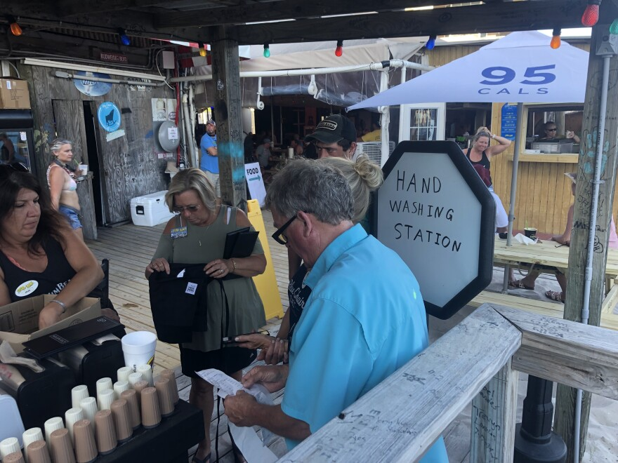 Servers go through a shift change at a makeshift hand-washing and sanitizer station outdoors at the Flora-Bama roadhouse in Perdido Key, Fla. Florida allowed restaurants to open this week at limited capacity and with new safety protocols.
