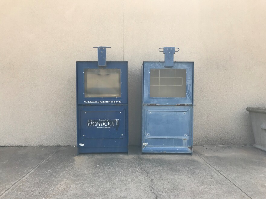 In this photo, two empty, dilapidated newspaper boxes sit side-by-side against a beige wall.