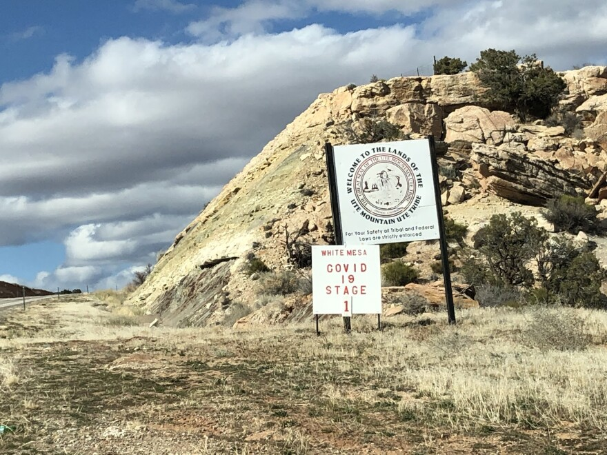"Photo of a sign that reads ""welcome to the lands of the ute mountain ute tribe"" and another sign that reads ""white mesa covid 19 stage 1"""