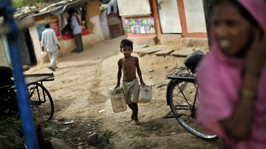 An Indian boy carries empty canisters to be filled at a water depot in a New Delhi slum. Data from India's latest census shows that although millions of Indians have access to technology such as TVs and cellphones, many millions more still lack basic amenities such as sanitation and water.