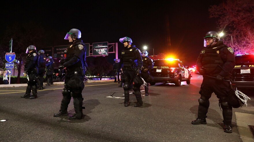California Highway Patrol officers block an interstate entrance as protesters march. Police use of deadly force became a focus for advocates in California after the district attorney declined to prosecute the officers who fatally shot Stephon Clark, an unarmed black man whose death sparked demonstrations in the state and across the country.