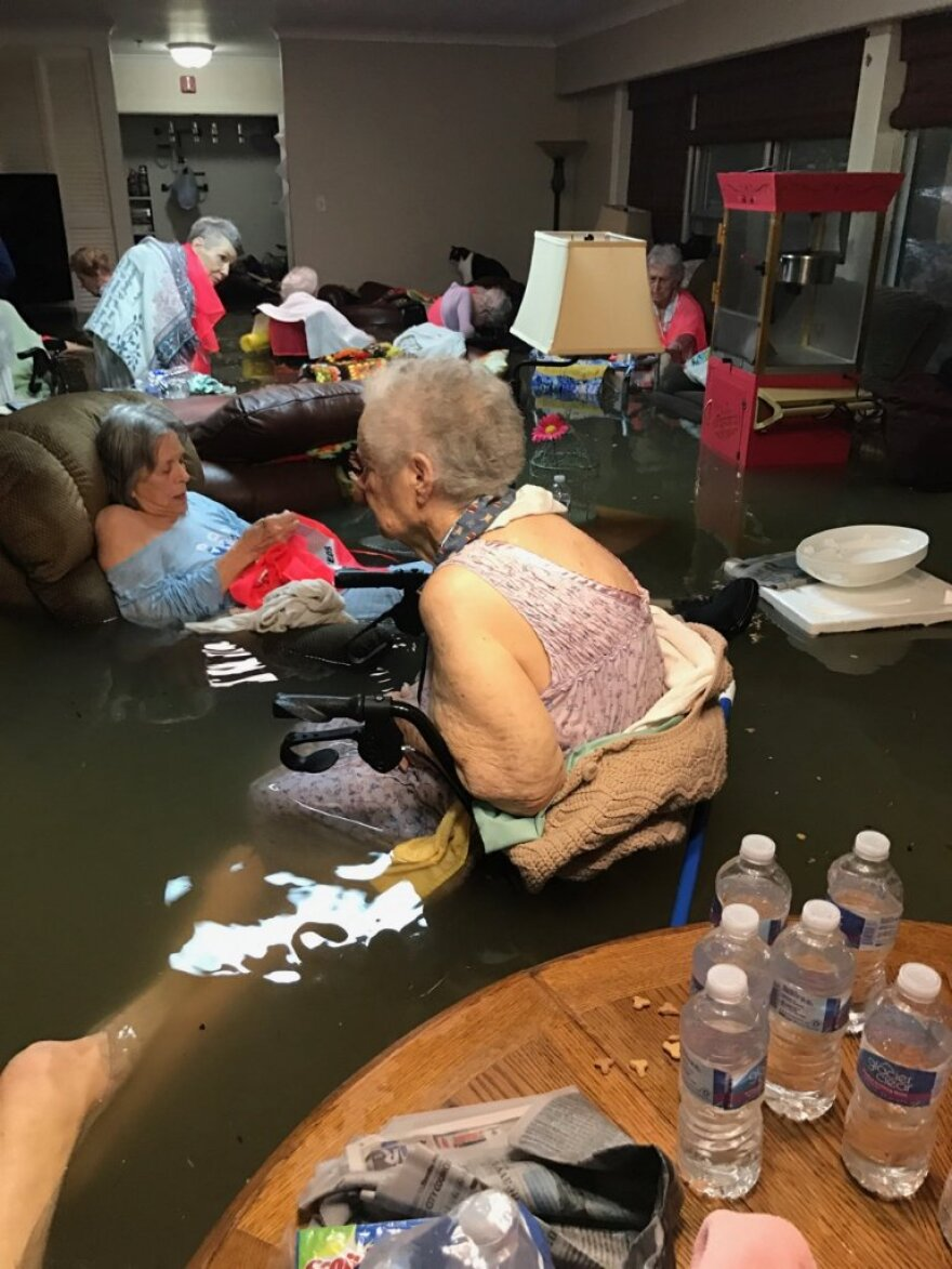 Residents sit in waist-deep floodwaters from Tropical Storm Harvey at the La Vita Bella assisted living facility in Dickinson, Texas.