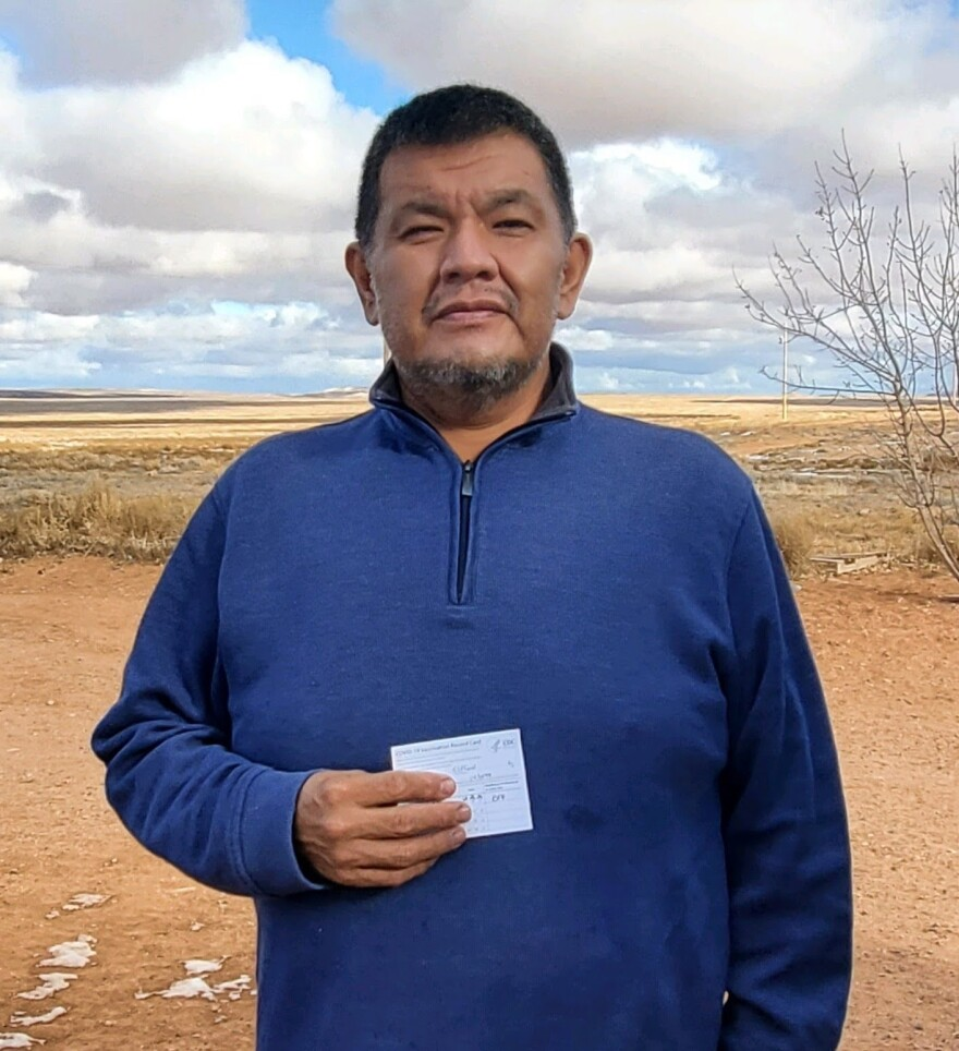 A Navajo man wearing blue sweater holds a small piece of paper
