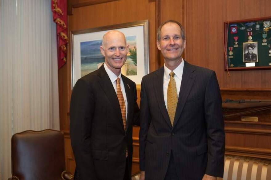Two bald men in dark suits pose side-by-side in a wood paneled office