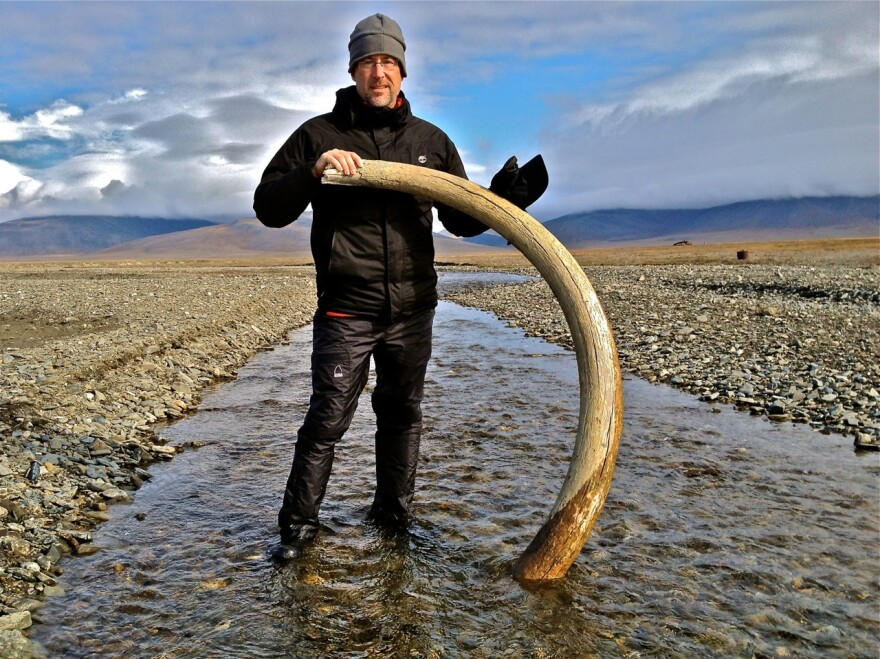Hampton Sides poses with a wooly mammoth tusk. According to <em>National Geographic,</em> scientists believe the island to be the last place mammoths lived before they went extinct.