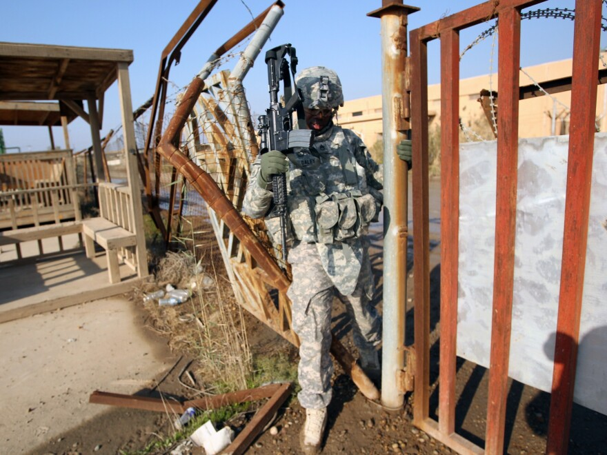 A U.S. soldier walks through a fence Monday at the Taji base complex north of the capital Baghdad.