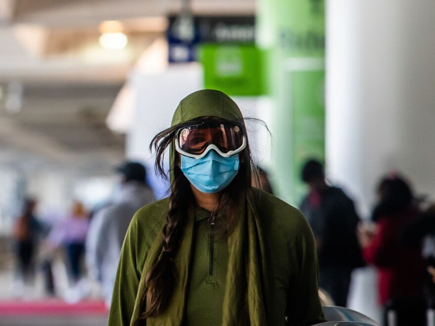 A woman wearing a face mask and goggles walks through LAX airport in Los Angeles on Friday.