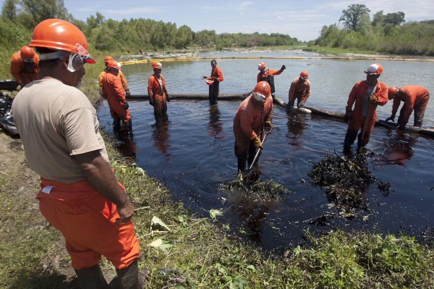 Workers from Pemex clean the San Juan river after an oil spill caused by fuel pirates who tapped into a pipeline in Nuevo Leon state, Mexico,  in August 2014. Fuel pirates are one of many above-ground complications in opening up the oil fields of northern Mexico.