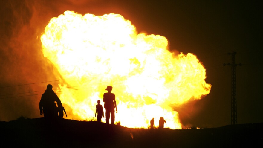 Bedouins watch flames rise in July 2011 after masked gunmen blew up a terminal of the Egyptian natural gas pipeline to Israel and Jordan. It was one of many attacks on the pipeline since the popular uprising that ousted longtime Egyptian leader Hosni Mubarak last year.