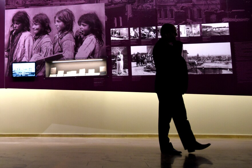 A man walks by photographs at the Armenian Genocide Museum in Yerevan, Armenia, on Tuesday. Armenians will mark the 100th anniversary of the killings on Friday.