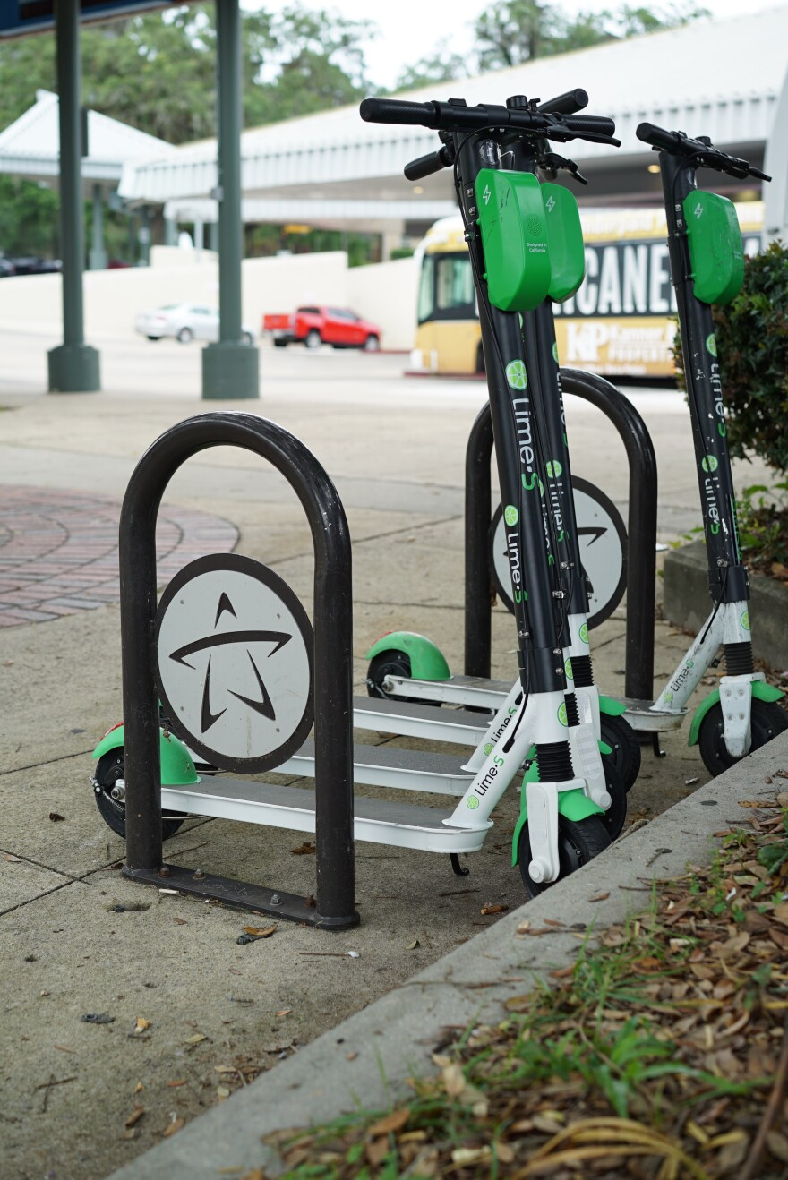 Four Lime e-scooters stand close together inside a bike rack.