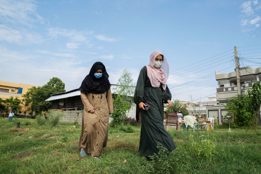 Laiba Atika (right), walks with her sister Maira Atika to check on the trees they had planted earlier in the season in the nearby park where they live in Mardan, Pakistan.