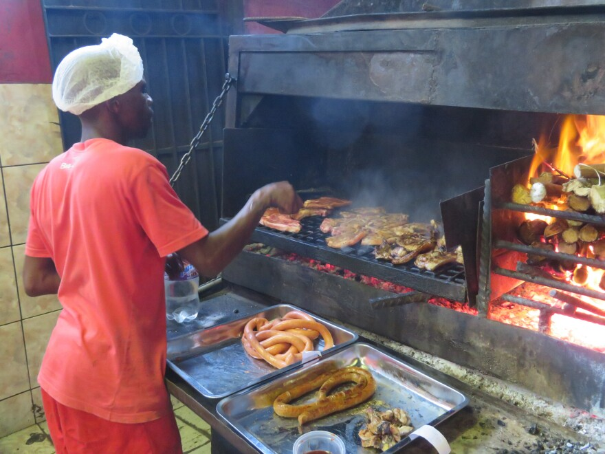 Braai is South African for barbecue. Here, meat is roasted over wood at Mzoli's, a popular butcher and grill in Gugulethu township.