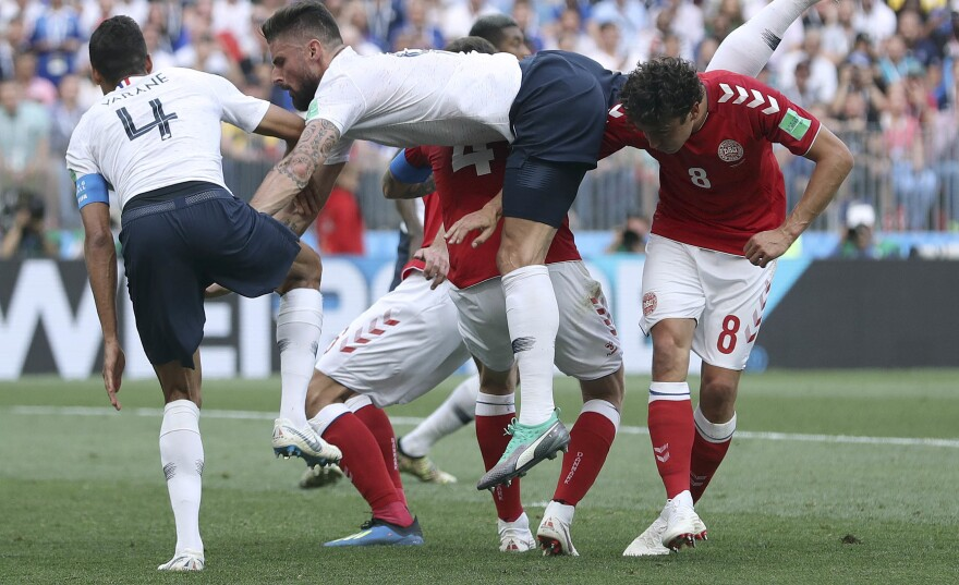 France's Olivier Giroud, center, goes down after a header during the group C match between Denmark and France at the 2018 soccer World Cup at Luzhniki Stadium in Moscow on Tuesday. The teams played to a scoreless tie — the tournament's first.
