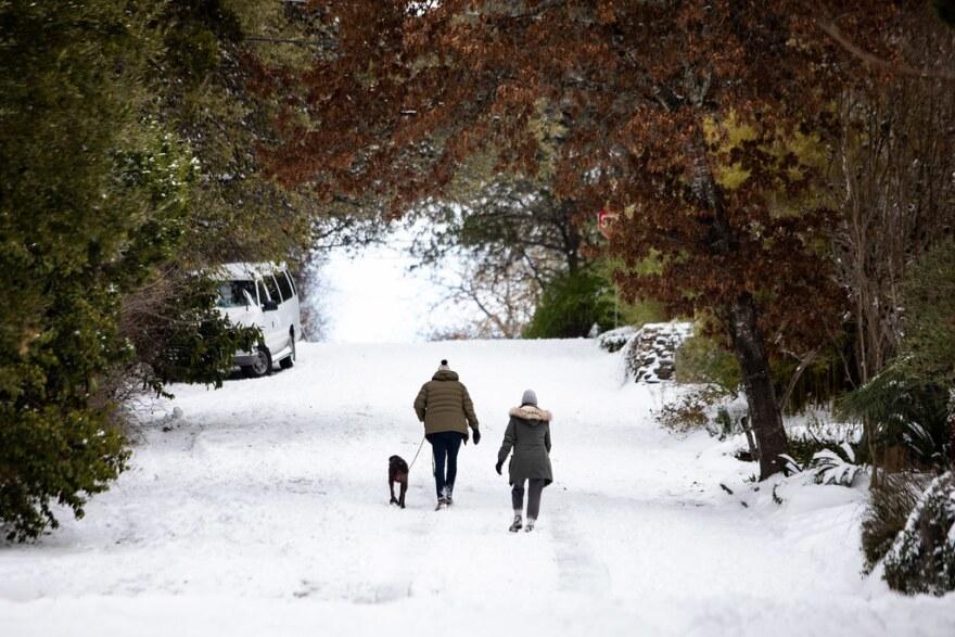 People walk over snow and ice in Austin's Travis Heights neighborhood Monday.