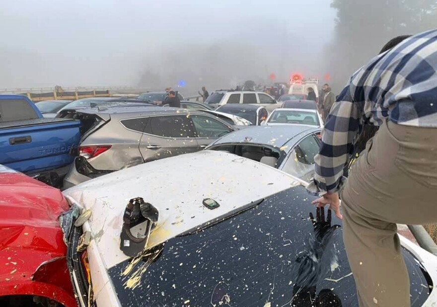 A person climbs over cars at the scene of a multivehicle pileup on Interstate 64 in York County, Va. on Sunday.