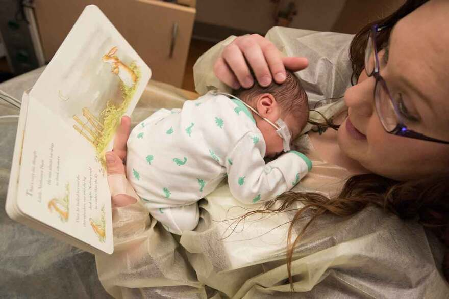 Nycole Tennant reads a book to her son Kainen in the neonatal intensive care unit at St. Louis Children's Hospital. Kainen and his twin sister, Kyzer, were born prematurely.