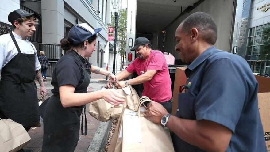 A Feeding Northeast FLorida team is pictured distributing meals in front of Bellwether in Downtown Jacksonville.